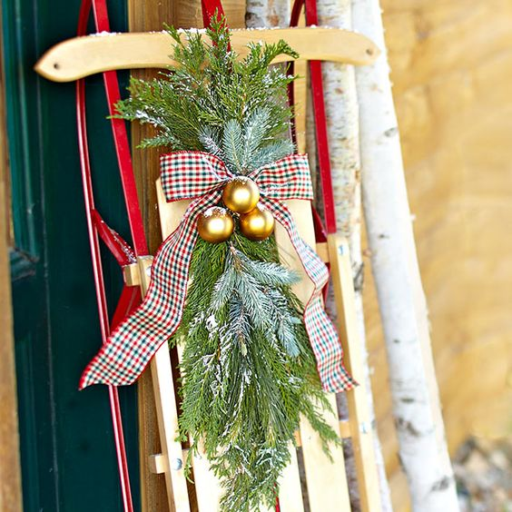 Create this easy greenery project in your home. Lean a favorite Christmas or winter object -- such as a vintage sled -- by your front door and adorn it with a cluster of greenery, ribbon, and ornament balls.