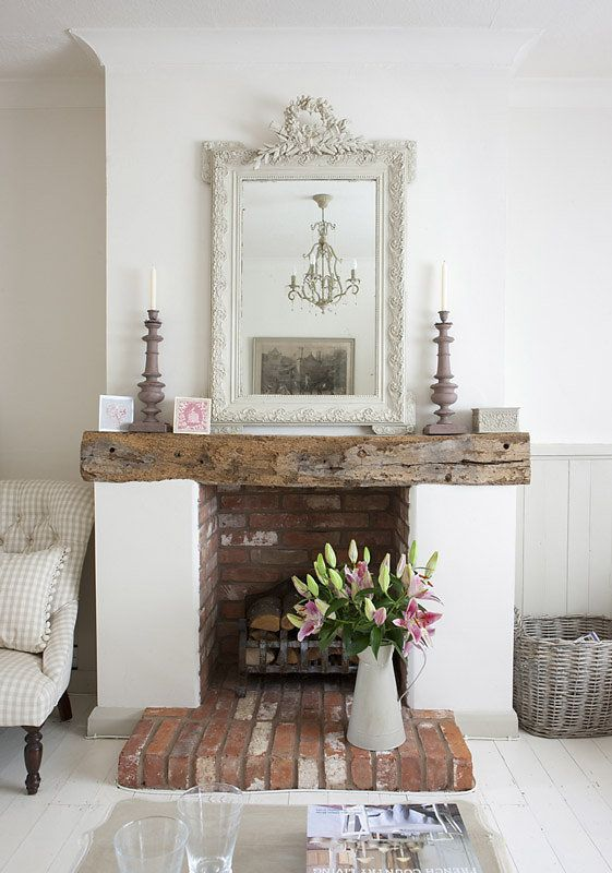 Farmhouse shabby chic living room with distressed brick, distressed wood mantle, antique white ornate mirror: