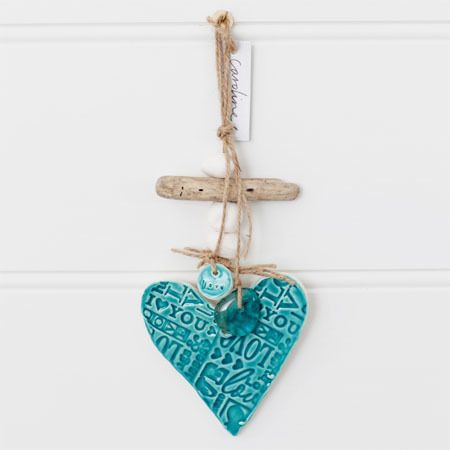 clay heart handmade in Australia    white earthenware clay glazed with a beautiful gloss turquoise glaze    words of love pressed into the clay    natural twine with clay pebble beads, driftwood and glass make up this beautiful wall hanging    you could personalise this gift by handwriting a message on the back (unglazed side) with a felt pen    each piece is handmade so no two pieces are ever the same    size of heart approximately     cm    overall size approximately      cm
