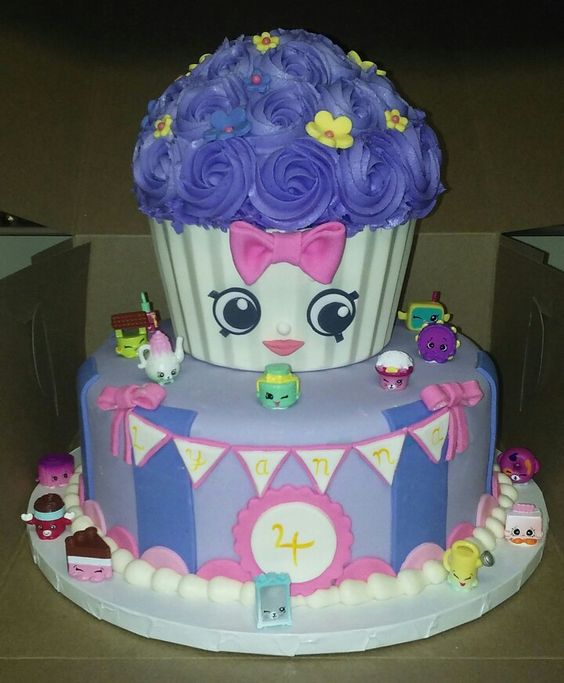My second Shopkins cake. The design was based on a picture my coworker sent. The giant cupcake liner was made of white chocolate using the pan as a mold, and the shopkins are actual shopkins. The face and all other decorations were done by hand.: