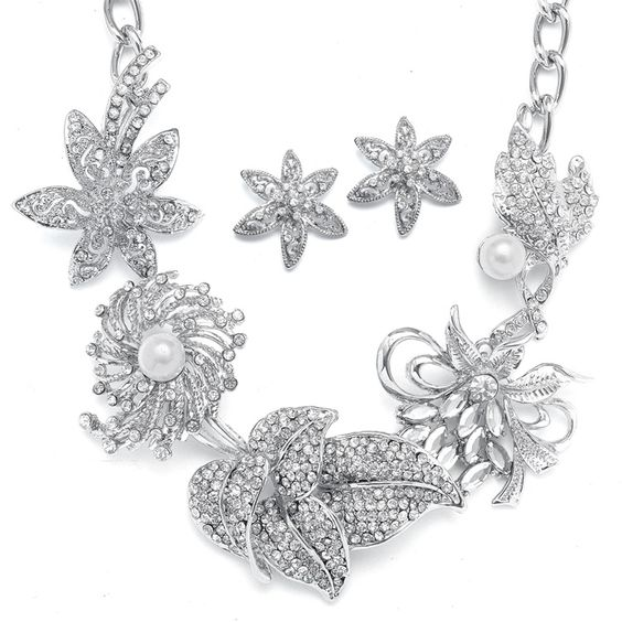 This unique jewelry design features flowers sculptured in silver rhodium and adorned with inlaid crystals and a touch of pearls!  www.thewhitedressbridal.com  Set $59.00