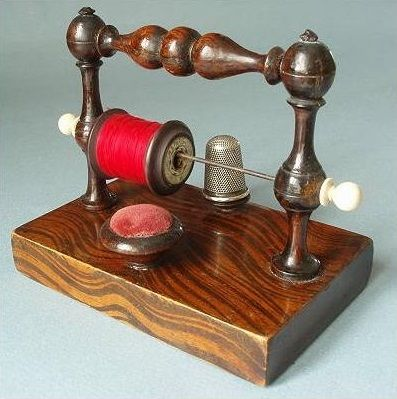 Early 19th century turned wooden reel holder incorporating a pin cushion and thimble rest.