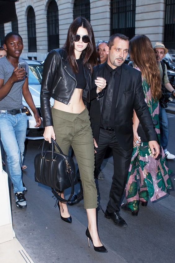 Kendall Jenner wears a black crop top, cropped moto jacket, olive green cropped pants, pumps, and a black duffle bag