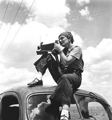 La photographe américaine Dorthea Lange (1895-1965) en position sur le toit d'une voiture, prête à déclencher.