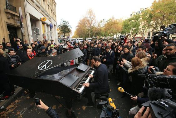 """Un anonyme a amené son piano à queue et joue """"Imagine"""", de John Lennon, à l'extérieur de la salle de concert Le Bataclan, le samedi 14 novembre 2015 à Paris."""
