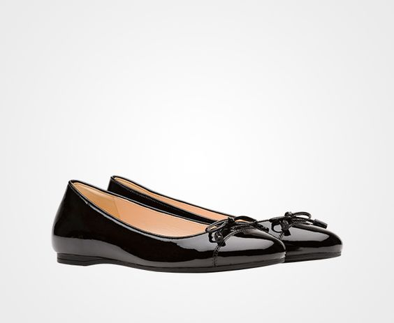 Prada: Patent leather ballerina with toecap  Bow with leather tassels  15 mm heel  Amber-colored lettering logo  Rubber sole