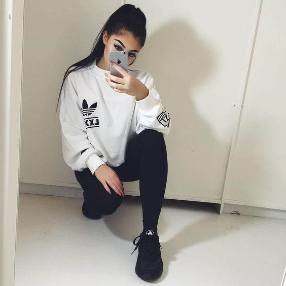 In this outfit the person wore an adidas white jumper,  black leggings and all black Nike huaraches.
