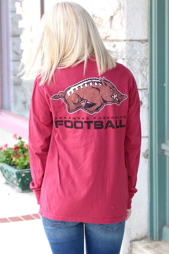 "Arkansas Razorback logo with the football stitch print inside it. ""Arkansas Razorback Football"" printed underneath. Long sleeve. Chili Pepper red in color. Comfort Color brand tee."