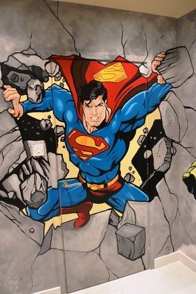 Part of the superhero (Marvel and DC mash-up) stairwell mural, Superman bursts through a wall.