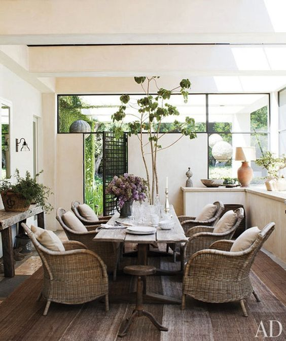 modern meets rustic. love this farm table and wicker chairs in this modern space.