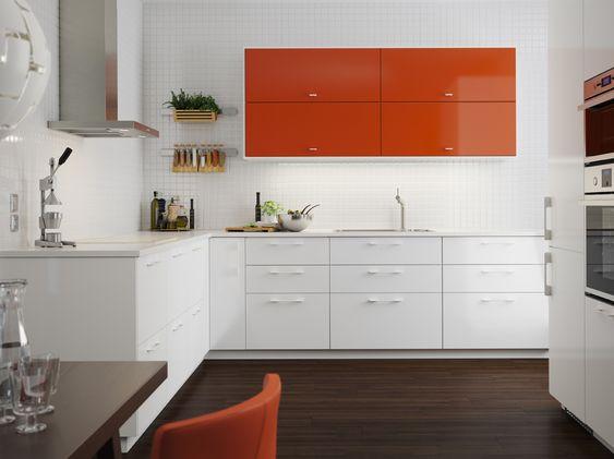 Cuisine de taille moyenne avec combinaison de portes orange brillant et de portes et tiroirs blanc brillant. Des appareils électroménagers en acier inoxydable complètent l'ensemble.