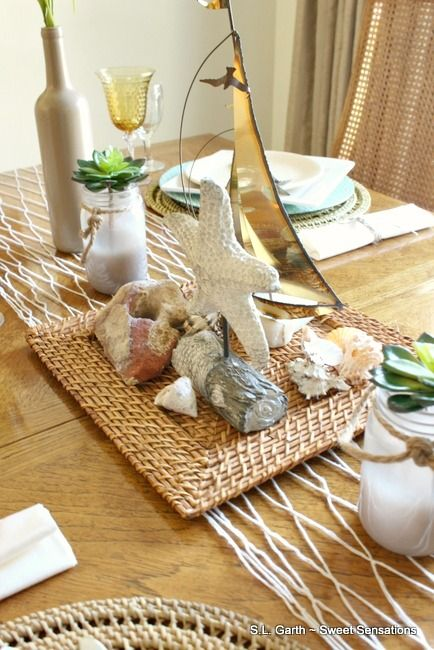When working with a theme, pick only a couple of elements to create the mood so you don't go overboard. Here, the centerpiece is the focus with this Coastal Table Décor.