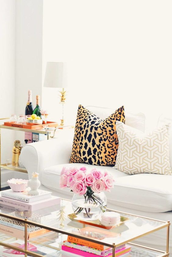 West elm coffee table in brass styled with coffee table books and fresh flowers, IKEA white sofa, leopard pillows