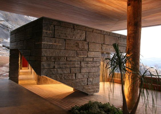 Timber and granite residence by Studio Seilern stands on a rocky ledge above an African dam.