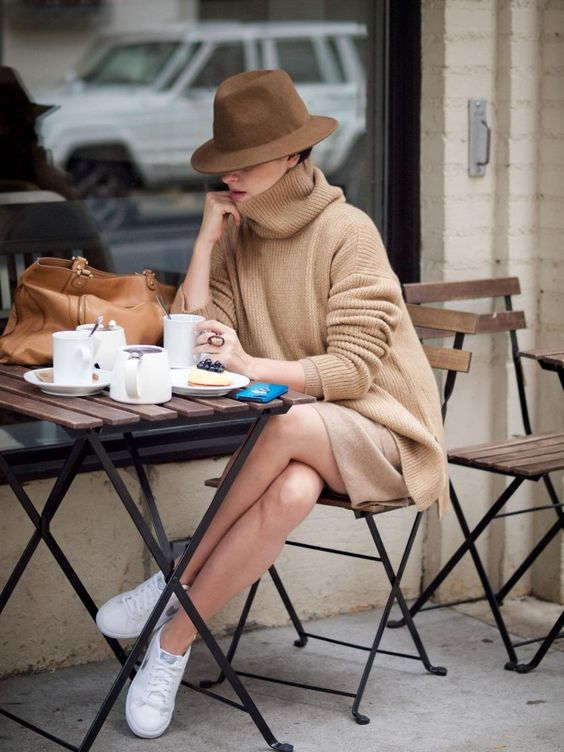 Street style in Paris - a beige sweater dress to white sneakers and a beige hat looks stylish and unexpected.:
