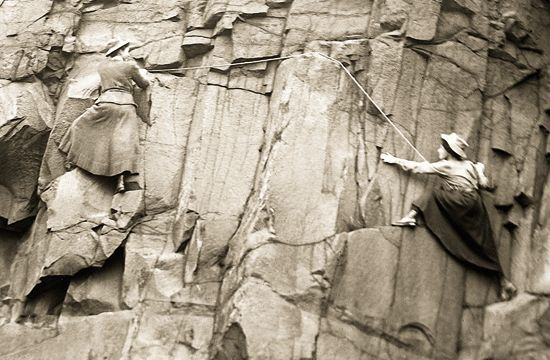 Perhaps a photo of Meta Brevoort climbing a rock face, and Kate following, around 1868 to 71. This would be a posed photo, or they'd both have on their wool trousers with gaiters or puttees. Kate didn't like this sort of climb, and preferred solo mountain walking, with only short scrambles over rocky outcrops when necessary.: