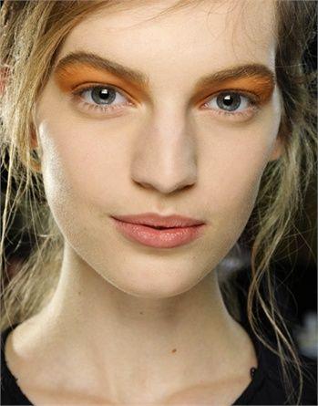Ombretto arancione su palpebra mobile e fissa, bocca rivestita da un velo di gloss naturale.