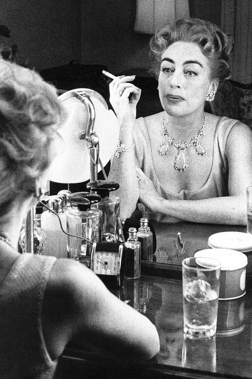 A middle aged Joan Crawford at her dressing table having a drink and smoking a butt, 1959