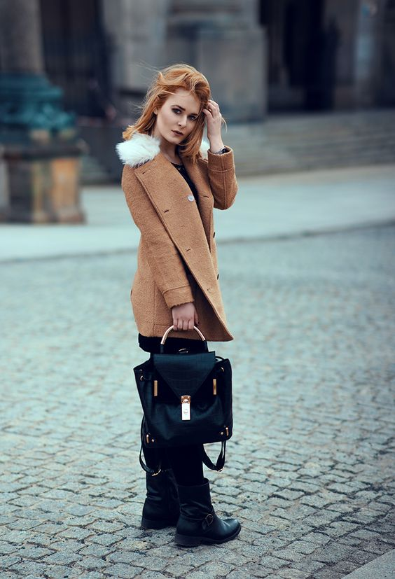 Wearing a black backpack with golden details and a cool winter jacket in Berlin