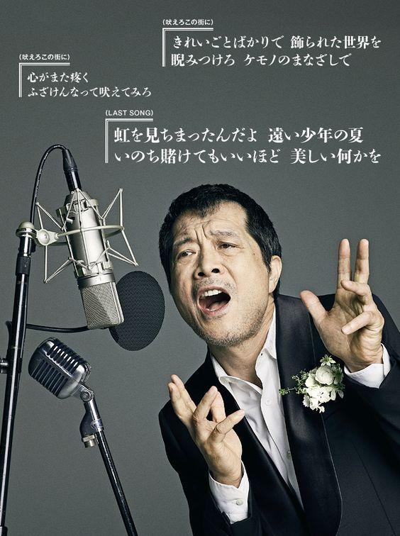 スーツ姿に胸に花を挿して歌っている矢沢永吉の画像