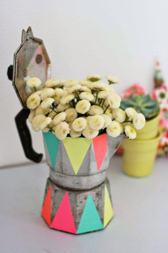 Une vieille cafetière relookée par des peintures fluos et transformée en vase.