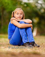 Teenage girl sitting on green meadow by Eduard Titov