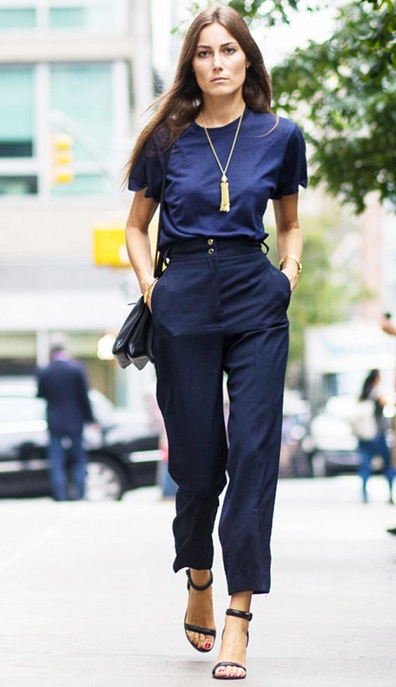 A navy blue t-shirt is tucked into cropped trousers, paired with a Céline shoulder bag and sandals: