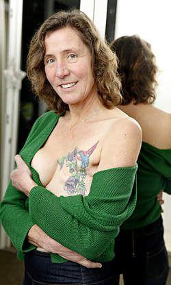 """Bewust één borst: 'Dit maakt het toch een beetje spannend' - AD.nl Met een tatoeage over haar litteken wilde Manon Bijl (54) een zichtbare betekenis geven aan haar borstamputatie. Volgens de Amerikaanse stichting P.ink helpen tatoeages borstkankerpatiënten hun verlies te accepteren. ,,Mijn kolibrie staat voor optimisme, voor vrolijkheid."""""""