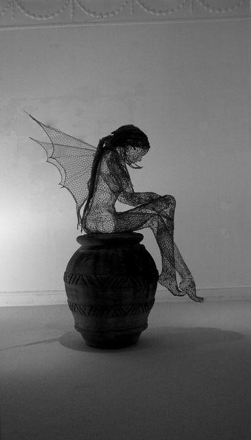 Title: Wood Cutters Sprite. by Derek Kinzett Medium: Wire sculpture. Dimensions: 130cm Height x 45cm Width x 100cm Depth. Weight: 5 Kg. Installation: Seated.