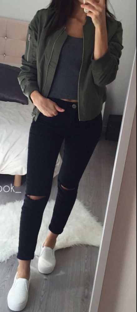 Hunter green bomber jacket with gold zippers, plain dark grey crop top, black ripped skinny jeans.