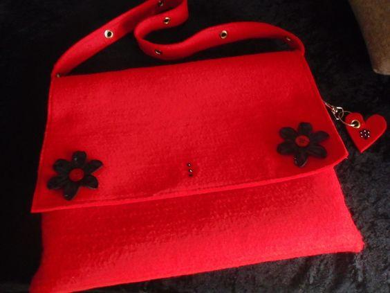 Chice rote Filzhandtasche mit kurzem Schulterriemen, in den goldfb, Ösen eingelassen sind. Schwarze Applikationen und Strass-Steinchen runden das Bild
