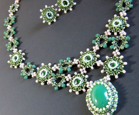 absolutely not pink but has soft opalized pink seed beads combined the greens of spring like apple blossoms. Bezels of seed bead embroidered Swarovski rivoli. Colorful OOAK seed bead jewelry created by BeadXilla