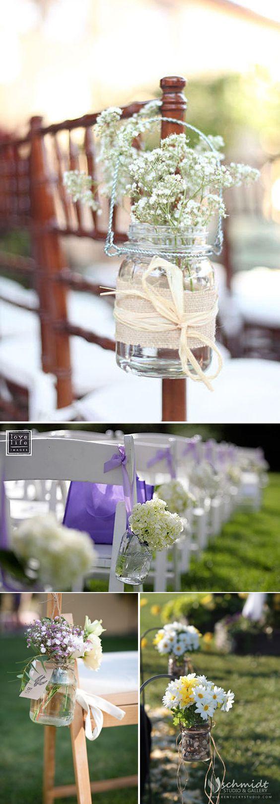 Preciosas botellas de cristal con florecillas de temporada para decorar los pasillos de la ceremonia: