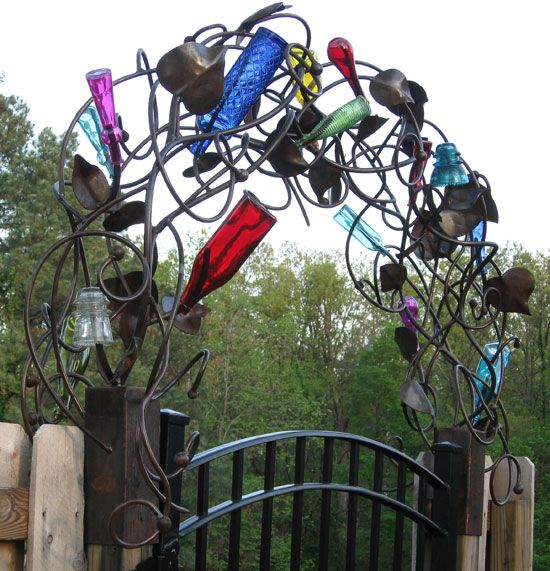 Whimsical and colorful garden gate entry arch made with different colored glass bottles and swirled metal wire (heavy!) plus other bits and objects.