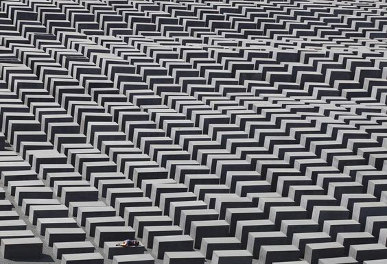 A girl rests on a plinth at Peter Eisenman's Holo­caust memo­r­ial in Berlin  (a provacative, uneven forest of 2,711 charcoal-​​grey rec­tan­gu­lar plinths) - REUTERS/​Tobias Schwarz