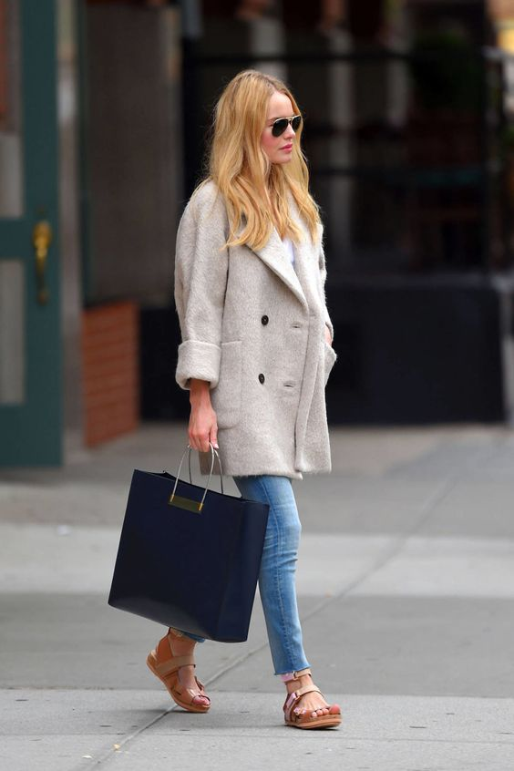 Kate Bosworth holds onto summer by styling her skinny jeans and MIH coat with a chic pair of flat sandals.