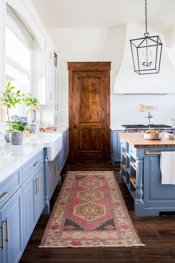 blue modern farmhouse kitchen with rustic industrial elements. Benjamin Moore Van Courtland Blue and Swiss Coffee, Calacatta marble with a mitered edge, brass Waterstone hardware, white farmhouse sink, white subway tile, the Darlana Lantern and Currey and Co Timpano pendents.