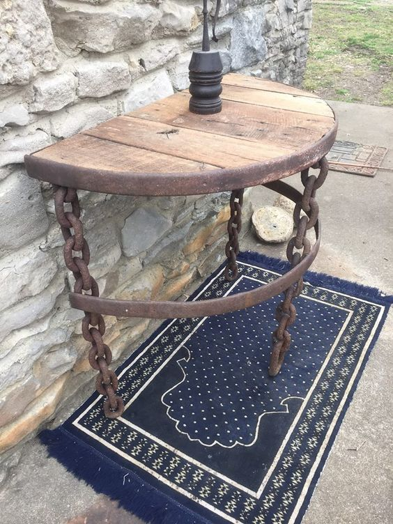 This is made from a 200-year-old hand-forged logging chain, an antique iron wagon wheel, and 100-year-old oak barn lumber. The chain was welded to create the legs. One of the most unique pieces I have ever  seen.
