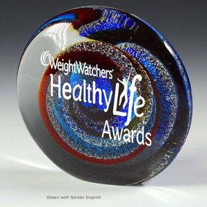 The Corinth Paperweight Award has a small flat edge section so it can stand upright or lay flat. It bursts with color and silver flecks to create a unique and interesting recognition statement. Available January 2013