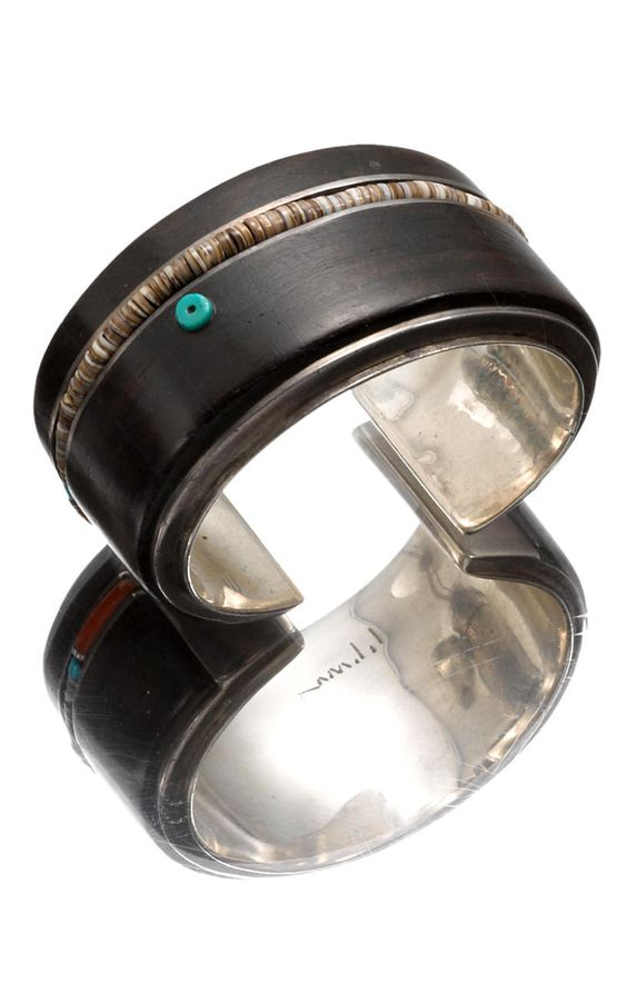 Cuff | Charles Loloma.  Sterling silver inlayed ironwood plaques bisected by a band of channel-set heishi beads anchored with coral and turquoise, a solitary offset disc bead as accent. |  1970s. | Evocative of a kachina mask