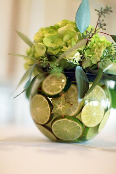 Bubble bowl centerpiece lined with slice limes and starfruit, green hydrangeas and seeded eucalyptus.