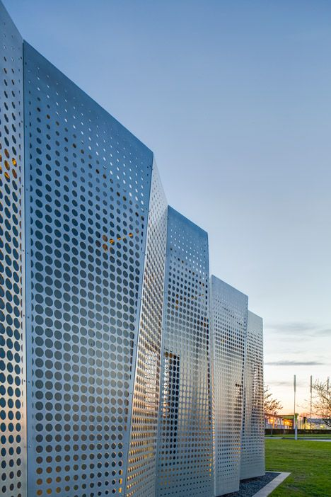 Perforated metal sheets concertina across the facade of an office ...