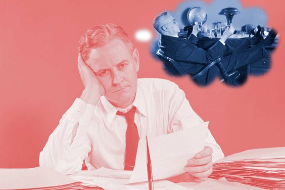 Unhappy overworked businessman sitting at desk holding papers