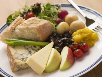 TraditionalPloughman's Lunch ... small mixed salad, branston pickle, piccalilli, pickled onions, beetroot slices, hard boiled egg, tomato, brie cheese, cheddar cheese, stilton cheese, double gloucester cheese, apple, pork pie, bread & butter
