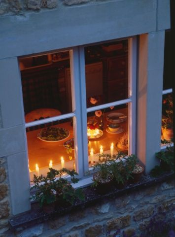 View into a kitchen window looking down at table surrounded by candles: