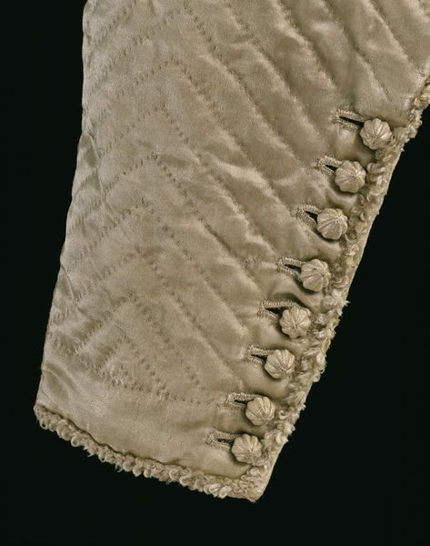 Detail of buttons.  Suit, 1635-1640.  England, Great Britain (made).  Ivory satin, quilted, with applied silk braid. | V Search the Collections