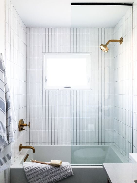 Vertical stacking tile + stack bond tile + white shower tile + brass shower head + large tub + window in shower + glass shower door + shower tub combo | Nyla Free Designs