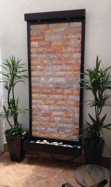 fuente de pared vertical con piedra arcoiris y jardineras