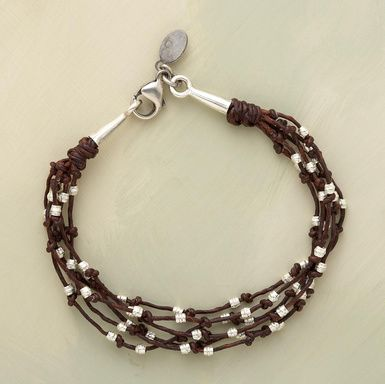 """Twig-like strands of waxed brown linen sprout etched sterling silver buds, each allowed freedom of movement between knots. Conical endcaps flank a lobster clasp. Handcrafted in USA. 7-1/2""""L."""