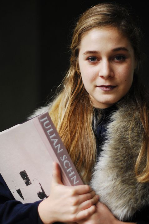 Harvard Student Sarah wears a blue fur lined rain coat tippet over a black and white vertical striped dress skirt and black rain boots. She is carrying a  julian schnabel painting book.